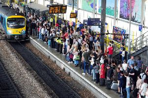 Passengers in Leeds await the arrival of a service to Manchester.
