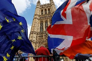 Pro-Brexit and anti-Brexit protesters hold flags as they demonstrate outside the Houses of Parliament in London (Photo by Tolga AKMEN/AFP/Getty Images