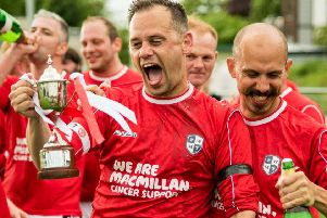 Organiser Adam Broadley lifts the Peter West Memorial Trophy after victory for his side in last year's match.