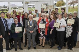Library staff and volunteers receive Summer Reading Challenge awards from Cllr Jim Clark, with Cllr Greg White, left.
