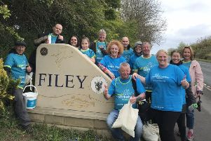 Chris Hewitt and his supporters pose for a picture at the Filey sign as they finish the 86-mile walk.