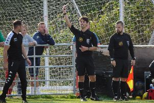 Furious Trinity boss Liam King is booked for protesting a late penalty decision.