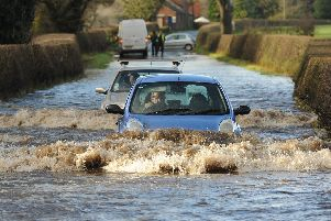 A car ploughs through flood waters in Garstang