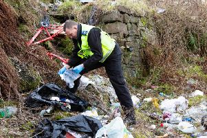 Community Safety Warden Craig Heywood, inspects rubbish at a fly tipping hot spot in Pellon