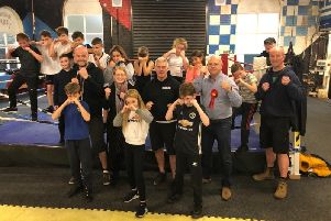 Mr Kemp poses with young members of the boxing club