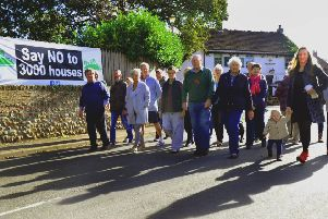 061017     Residents   walking on the  main street in Green Hammerton , in front of one of the banners protesting  against the 3,000 new homes. .      YP Ftrs.