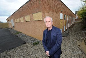 Paul Cairns at the rear of the building showing how many windows have been smashed. Picture: Gerard Binks.