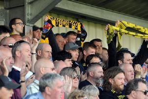 Harrogate Town supporters cheer on their team at the CNG Stadium.
