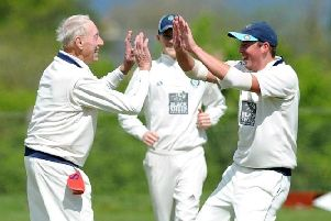 Experienced Masham bowler Derek Chapman, left, is congratulated after taking the first of his four wickets against West Tanfield. Picture: Gerard Binks