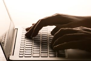 A woman's hands on a laptop keyboard.