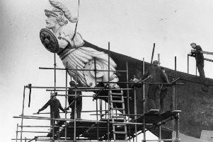 HMS Warrior's figurehead, a worthy addition to the restoration progress, is hoisted into position in 1985.