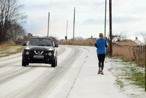 A jogger passes a motorist on a snowy road.