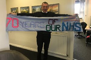 Mike Hill with the Heugh Yarners. 70th anniversary of the NHS banner.