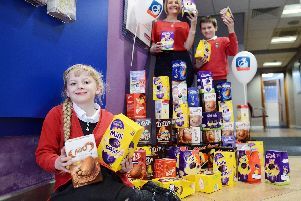 Tracey McDermott (Member representative from Nationwide Building Society) handing over Easter eggs for the Foodbank to Holy Trinity CofE Primary School pupils Scarlette Mason (9) and Benjamin Cooper (9).