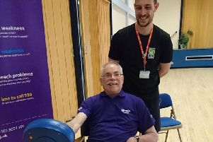 A stroke survivor learning about physiotherapy and aftercare using the MOTOmed bike at a pop up at Community Hub South.