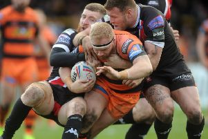 Oliver Holmes is tackled by Salford's Jackson Hastings and Josh Jones on his return to action. Picture: Tony Johnson