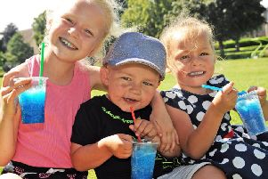 Ava Bradley, 7, her 2 year old brother Alfie and 5 year old sister Olivia keep their cool with slush drinks whilst out at Titchfield Park.