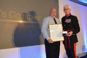 Kirk Hallam bouncer Sean Moore, left, receiving the Queen's Commendation for Bravery from Vice Lord-Lieutenant John Wilson,