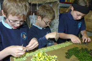 Brandon Townsend, Ben Willis and Charlotte Bonsall from Stoney Middleton Primary School work on a well dressing at the Moon Inn in 2007.