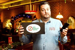 A Frankie & Benny's employee holding a no-phone zone box