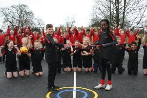 Year six pupils Max and Eniola  cutting the ribbon to officially open the MUGA along with other members of the schools Sports Council.