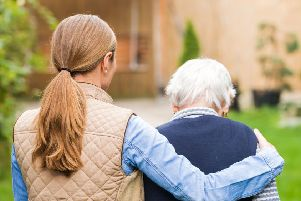 STOCK PHOTO: A young carer walking with an elderly woman.