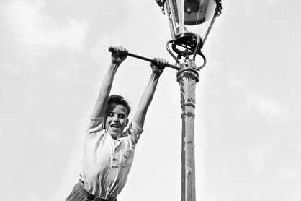 Swinging on the bar of a gas lamppost without a rope
