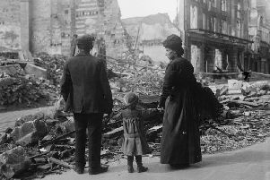A refugee family returning to Amiens, looking at the ruins of a house, September 17, 1918.  IWM (Q 11341)