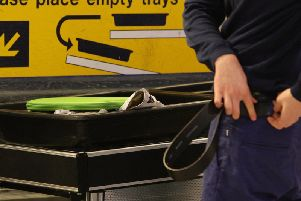 A passenger replacing a belt after having passed through security at Manchester Airports Terminal 1