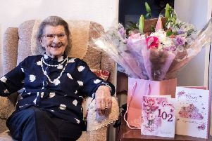 Anne Lane celebrating her 102nd birthday with flowers presented to her by her carers from All About You Care Services. Photo credit: Erynn Pope.
