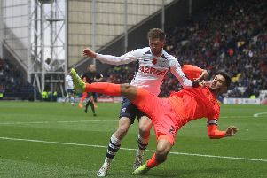 Preston winger Tom Barkhuizen competes for the ball against Huddersfield