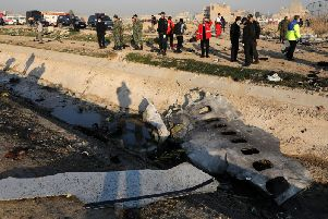 Debris is seen from an Ukrainian plane which crashed as authorities work at the scene in Shahedshahr, southwest of the capital Tehran, Iran, Wednesday, Jan. 8, 2020. A Ukrainian airplane carrying 176 people crashed on Wednesday shortly after takeoff from Tehran's main airport, killing all onboard. (AP Photo/Ebrahim Noroozi)
