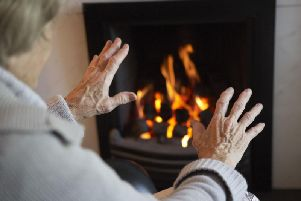 A pensioner warms her hands