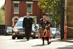 A piper leads Jim Bryson's funeral cortege into Fulwood Barracks