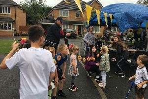 Children enjoy a game of Doughnut bobbing at the first street party