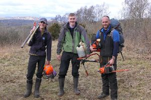 RSPB volunteers Cal Shipton and Connor Duhig with RSPB Estate Worker Richard Smith at work at Warton Crag nature reserve near Carnforth