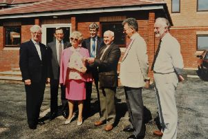The builder of Derian House, Bert Ainscough handing over the keys to Margaret Vinten accompanied by the Trustees: Douglas McMillan, Rick Thomas, Alan Chesters, who was Bishop of Blackburn, and Leo Duffy, in 1993