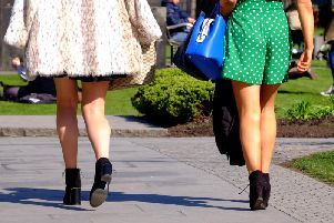 Two women wearing short skirts walk in the sunshine as upskirting, the invasive practice of taking an image or video up somebody's clothing, becomes a specific criminal offence in England and Wales, punishable by up to two years in custody.