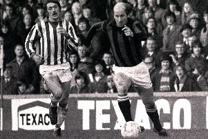 Bobby Charlton dons a red and black away kit while playing for Preston North End in the 1970s