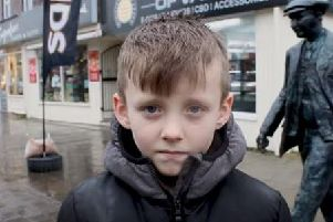 Lewis Anderson, eight, on film in front of the Leyland Motors man statue