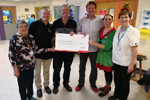 Mick Howarth, Frank Towers and Phil Alcock hand over a cheque to Rookwood A ward at Chorley Hospital after cycling from Denver to Ontario