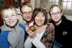 Elizabeth Dee shows off her Swimarathon medal to  husband Justin and sons Oliver and William