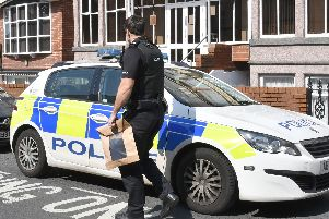 A police officer outside the Rooms Inn hotel in Albert Road, Blackpool, carrying an evidence bag after a girl, two, fell from a second-floor window shortly before 9am on Tuesday, August 20, 2019 (Picture: Dave Nelson)