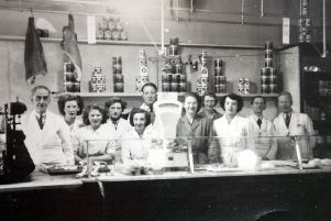 Well staffed: This picture of Brough's Grocers in Daisy Hill shows just how many people used to work in food shops before self service was introduced. Dorothy Heaton is the one wearing the dark uniform in the centre. Other staff who handled food wore white, but because she worked in the office, she wore green.