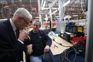 Jeremy Corbyn shares a packet of sweets with a factory workers in Wakefield