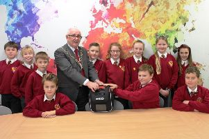 Coun Tommy Mulvenna, Chairman of North Tyneside Council, presents a defibrillator to staff and pupils at Wellfield Middle School in Whitley Bay.