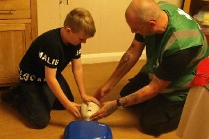 Lee Fraser, 10 learns how to assess a patient with Derrick Tait during a children's first aid session at The Oaks Care Home.