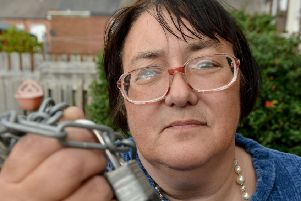 Annette Eversson holding the lock and chain that was cut off her Mobility Scooter. Picture by FRANK REID