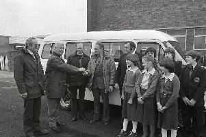 Mr Peter Healey of Bradshaws Motor House, hands over the keys of a new school minibus to headmaster Mr Pearce, watched by Mr David Saul, PTA chairman (left), Canon David Rees, Mr Mike Slater, PTA secretary and some of the pupils at Priory High School in Penwortham