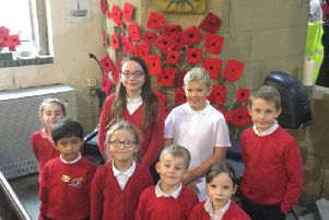 Some of the pupils from Earby Springfield Primary School pictured with the woven poppies they made on display.